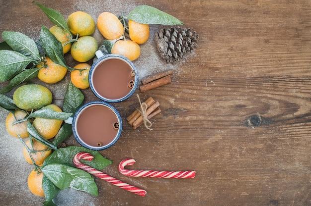 Cornice di natale o capodanno. mandarini freschi con foglie, bastoncini di cannella, pigna, cioccolata calda in tazze e bastoncini di zucchero su legno rustico, vista dall'alto