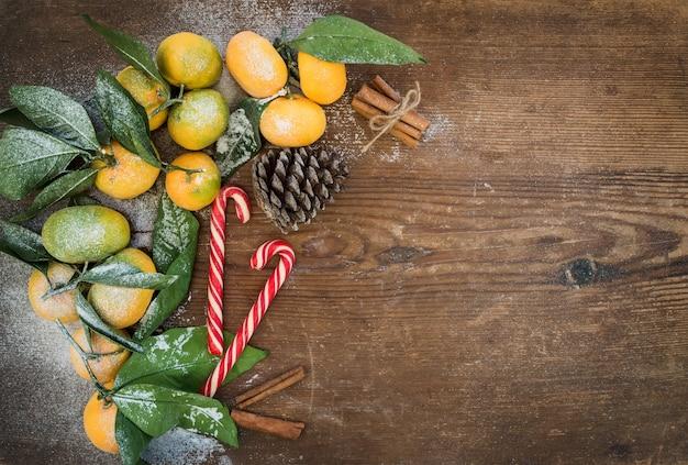 Cornice di natale o capodanno. mandarini freschi con foglie, bastoncini di cannella, pigna e bastoncini di zucchero su legno rustico, vista dall'alto