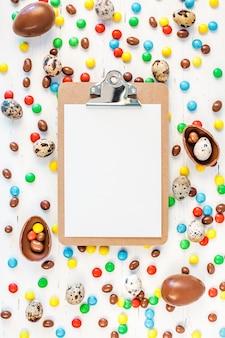 Cornice di pasqua con uova di cioccolato, caramelle colorate