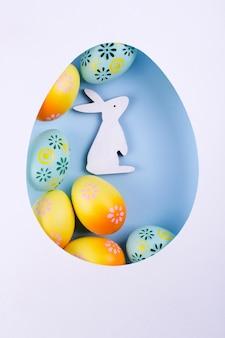 Cornice di pasqua fatta di carta, colorate uova di gallina dipinte, coniglietto di legno bianco su sfondo blu. vista piana, vista dall'alto, copia spazio