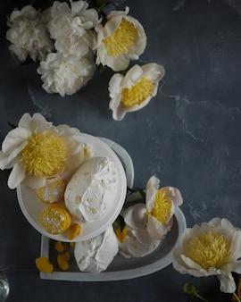 Cornice di peonie bianche e torte di meringa alla vaniglia su sfondo blu delicato matrimonio