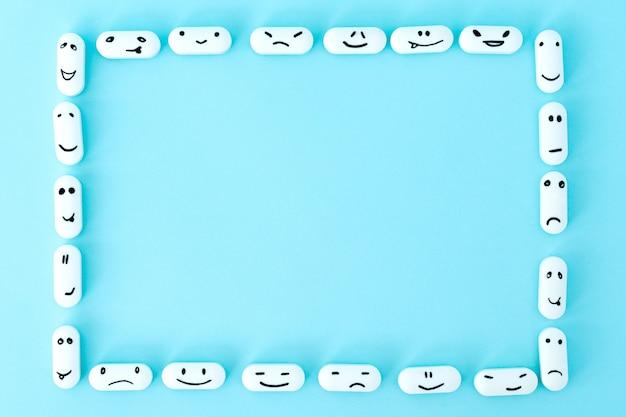 Cornice di pillole con facce buffe su sfondo blu
