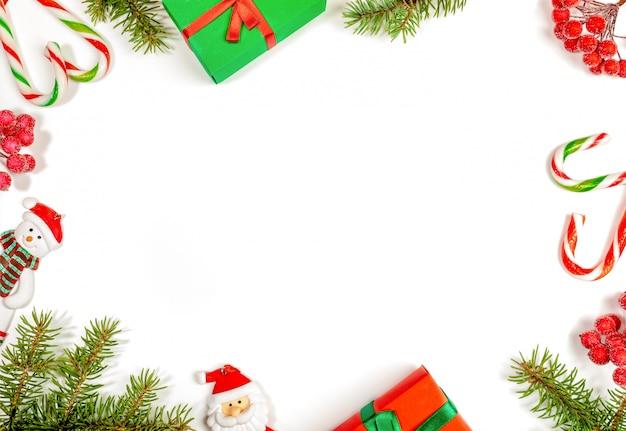 Cornice di rami di abete, bacche rosse, giocattoli di natale babbo natale e pupazzo di neve, scatole regalo, bastoncini di zucchero su bianco