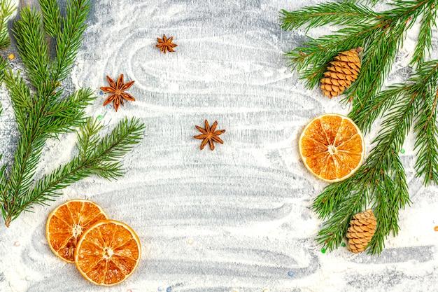Cornice di rami di abete, coni, anice stellato, cannella e arance secche su uno sfondo di farina.