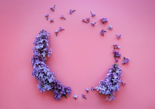 Cornice di rami e fiori di lilla su una rosa a forma di cerchio