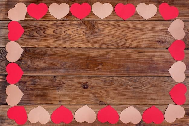 Cornice di san valentino con cuori rossi su fondo in legno in stile vintage
