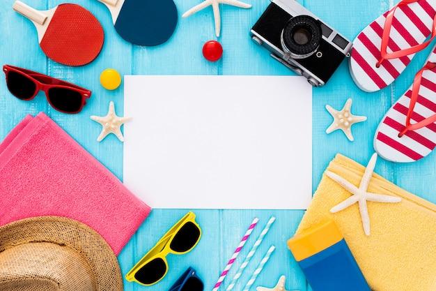 Cornice di sfondo estivo, carta bianca, spiaggia di sandalo, cappello, stelle marine su legno blu