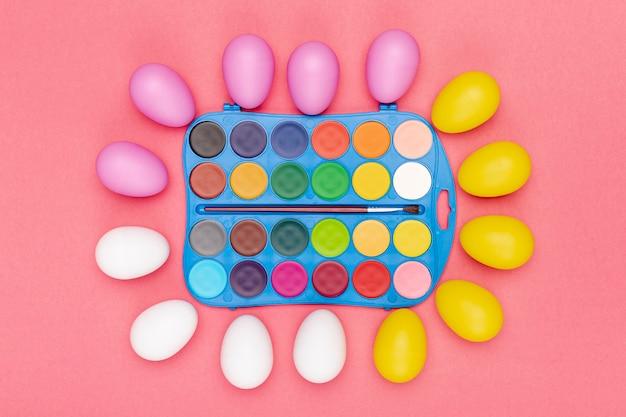 Cornice di uova con acquerelli sul tavolo