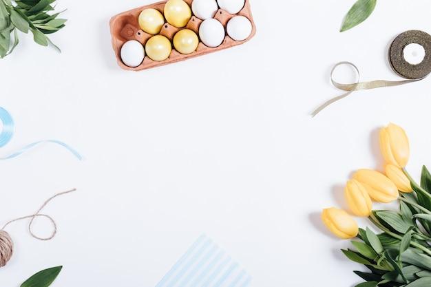 Cornice di uova di pasqua, fiori gialli, scatole di regali e nastri