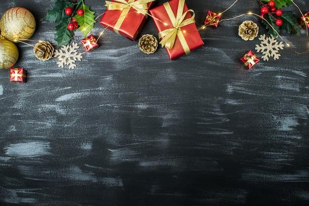 Cornice di vacanze di natale con palle di natale, regali, pigne, vischio, fiocchi di neve e luci di natale su uno sfondo scuro con texture