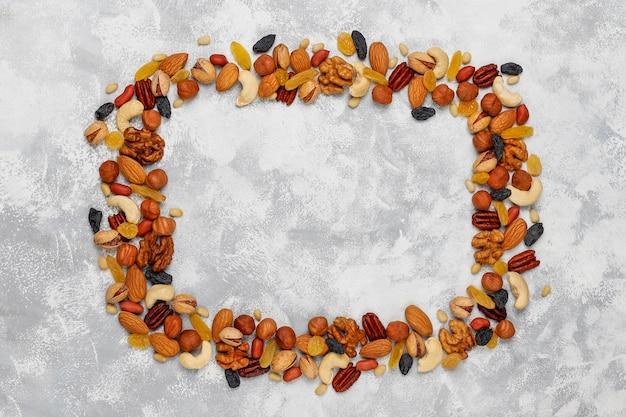 Cornice di vari tipi di noci, anacardi, nocciole, noci, pistacchi, noci pecan, pinoli, arachidi, uvetta. vista dall'alto