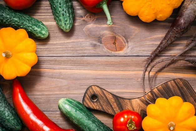Cornice di verdure fresche - zucca, cetrioli, pomodori, zucchine, peperoni su un tavolo di legno