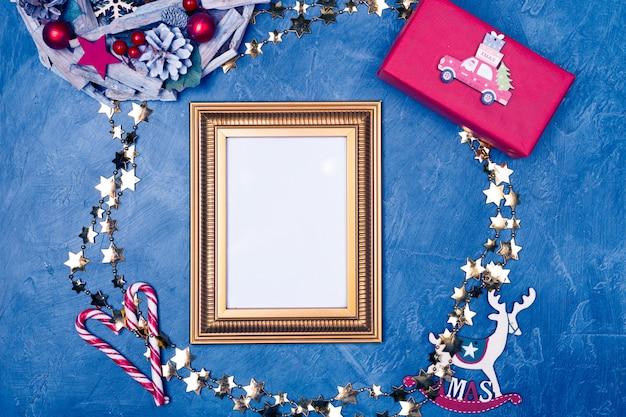 Cornice dorata con carta bianca su sfondo blu scuro, circondato da elementi natalizi spazio testo colore tendenza