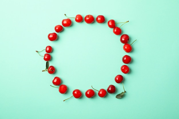 Cornice fatta di ciliegia rossa su sfondo menta