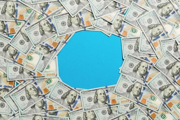 Cornice fatta di dollari con copyspace nel mezzo. vista superiore dell'affare sull'azzurro con copyspace