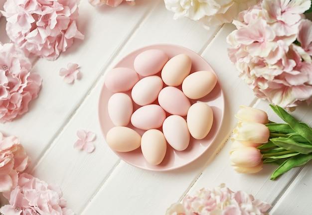 Cornice fatta di fiori di ortensia rosa e beige, uova rosa e tulipani gialli