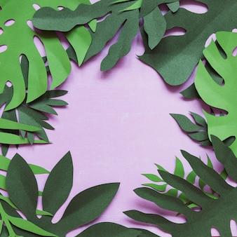 Cornice floreale decorativa creativa artigianale fatta di fiori e foglie di carta, carta per invito con varie foglie su un blu. flat lay.