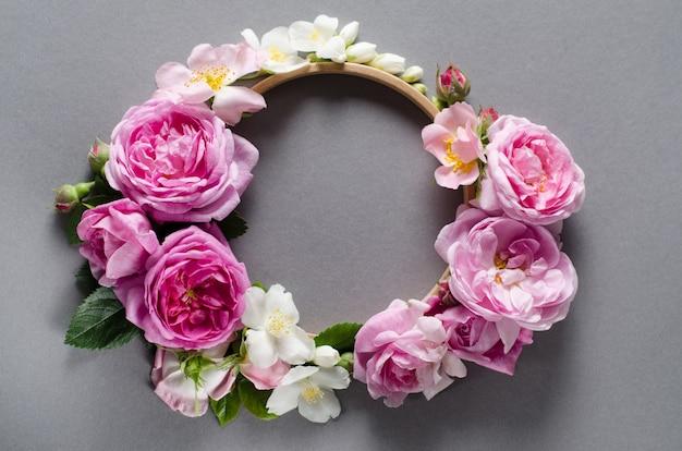 Cornice floreale fiori di rosa su uno sfondo grigio. distesi