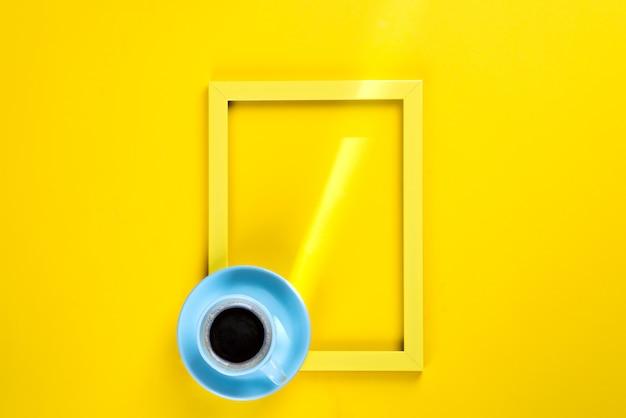 Cornice gialla con un raggio di sole e una tazza di tè su di esso, vista dall'alto su uno sfondo giallo, posto per il testo