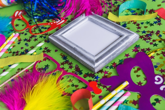 Cornice grigia con coriandoli, vetri colorati e bastoni