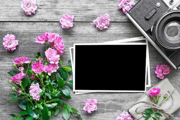 Cornice in bianco e retro macchina fotografica con i fiori della rosa di rosa e il contenitore di regalo.