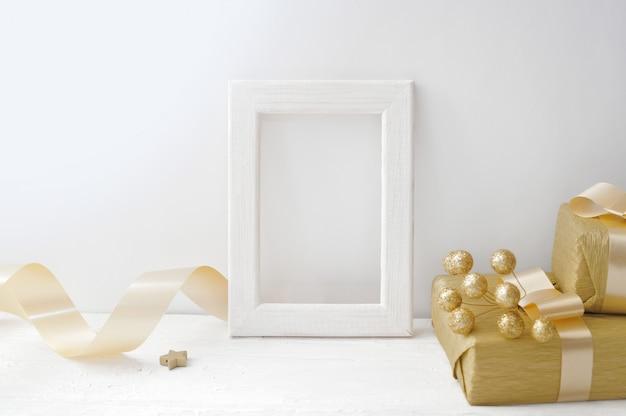 Cornice in legno bianco di natale con un nastro dorato e una confezione regalo