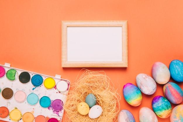 Cornice in legno bianco vuoto con scatola di pittura ad acquerello e uova di pasqua su uno sfondo arancione