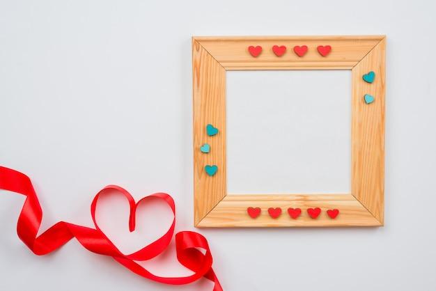 Cornice in legno decorata con cuori e cuore foderato con nastro rosso