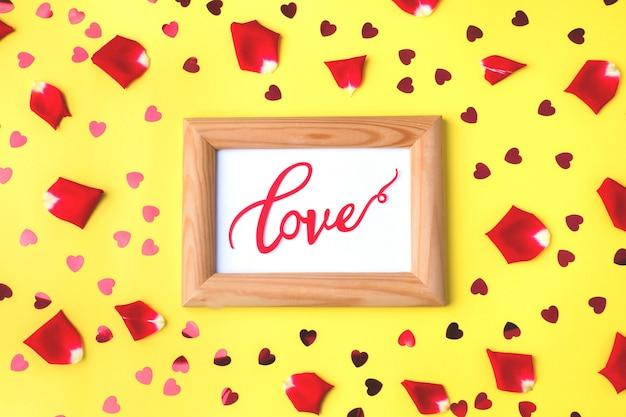 Cornice in legno e la parola amore, petali di rose e cuori rossi.