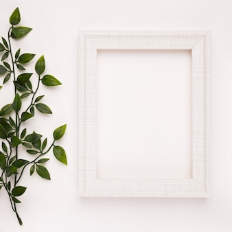 Cornice in legno vicino i ramoscelli su sfondo bianco