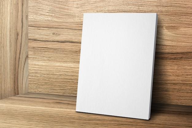 Cornice in tela bianca vuota che si appoggia al muro di legno e pavimento in legno