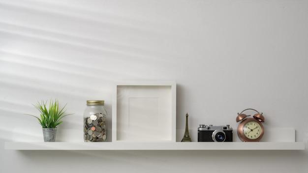 Cornice, macchina fotografica e decorazioni vuote sullo scaffale bianco con la parete bianca