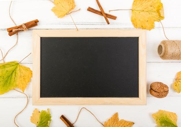 Cornice minimalista circondata da foglie con mock-up