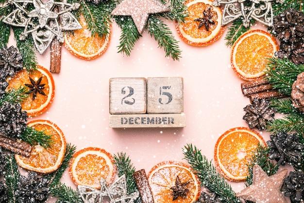 Cornice natalizia naturale di arance secche fette e decorazioni. calendario 25 dicembre. tonalità vintage.
