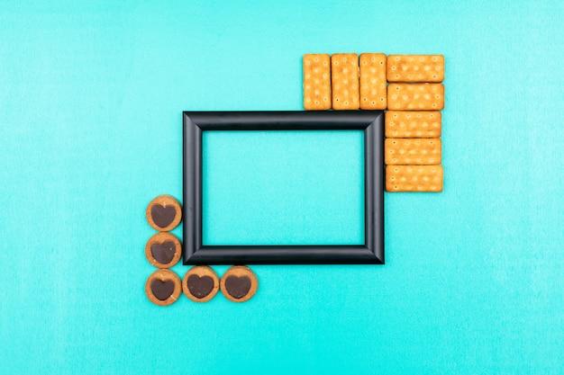 Cornice nera vista dall'alto con biscotti e copia spazio sulla superficie blu