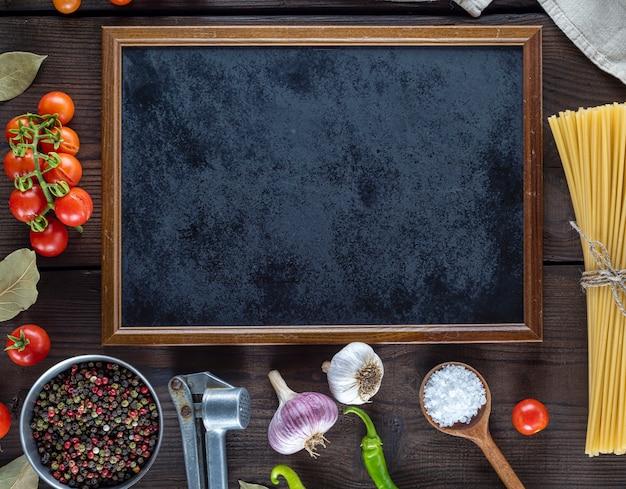 Cornice nera vuota e ingredienti per cucinare la pasta