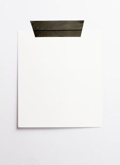 Cornice per foto in bianco della polaroid con le ombre molli e nastro adesivo nero isolato sul fondo del libro bianco