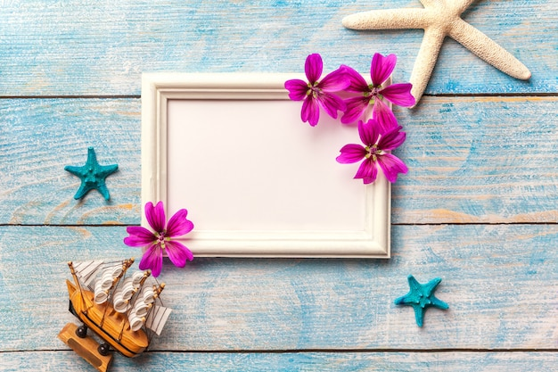 Cornice per foto in legno bianco con fiori viola su sfondo blu vecchio malandato con spazio di copia.