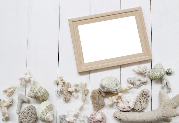 Cornice per foto in legno su un pavimento in legno bianco e conchiglie e barriere coralline.