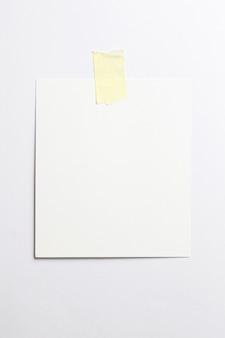 Cornice per foto polaroid in bianco con ombre morbide e nastro adesivo giallo isolato su sfondo di carta bianca
