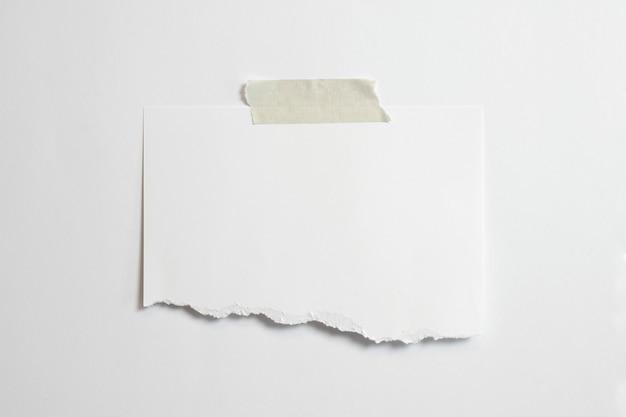 Cornice per foto strappata in bianco con ombre morbide e nastro adesivo isolato su sfondo di carta bianca