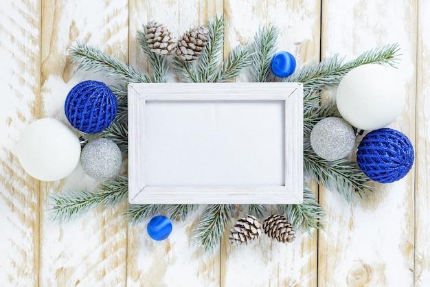 Cornice per foto tra decorazioni natalizie, con palline blu e pigne su un tavolo di legno bianco. vista dall'alto, cornice per copiare lo spazio