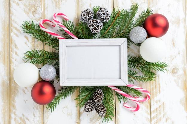 Cornice per foto tra decorazioni natalizie, con palline colorate e bastoncino di zucchero su un tavolo di legno bianco. vista dall'alto, cornice per copiare lo spazio.