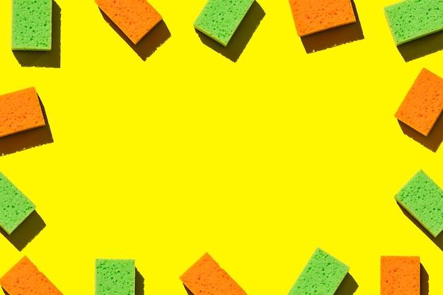 Cornice per iscrizioni da spugne multicolori per lavare i piatti su uno sfondo giallo