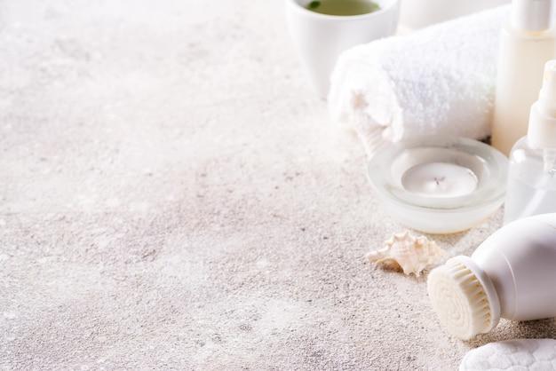 Cornice per la cura del viso con cosmetici bianchi con set da tè su pietra chiara