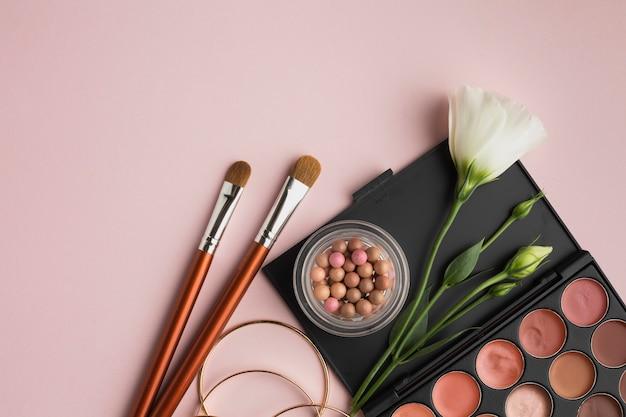 Cornice piatta con palette di bellezza e pennelli