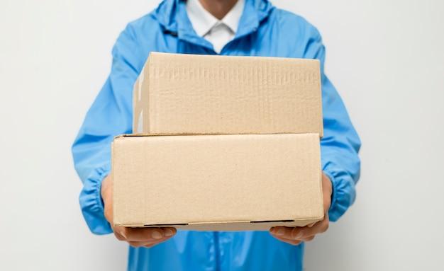 Cornice ritagliata di un corriere di consegna su bianco con scatole in mano.