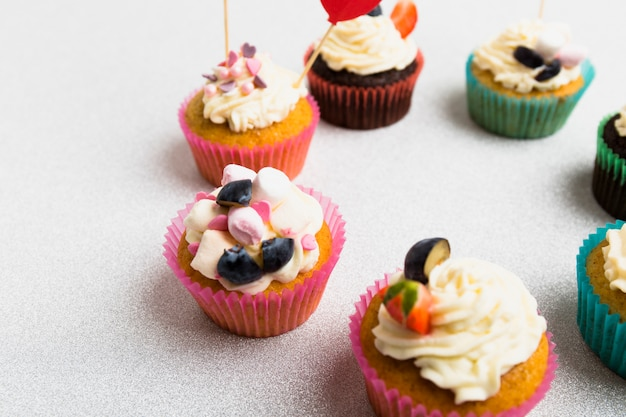 Cornice rotonda da piccoli cupcakes sul tavolo bianco