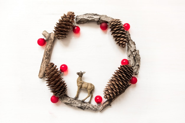 Cornice rotonda fatta di corteccia, pigne e palle rosse. composizione di natale piatto invernale laici