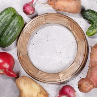 Cornice rotonda in legno e brutte verdure adagiate attorno ad essa